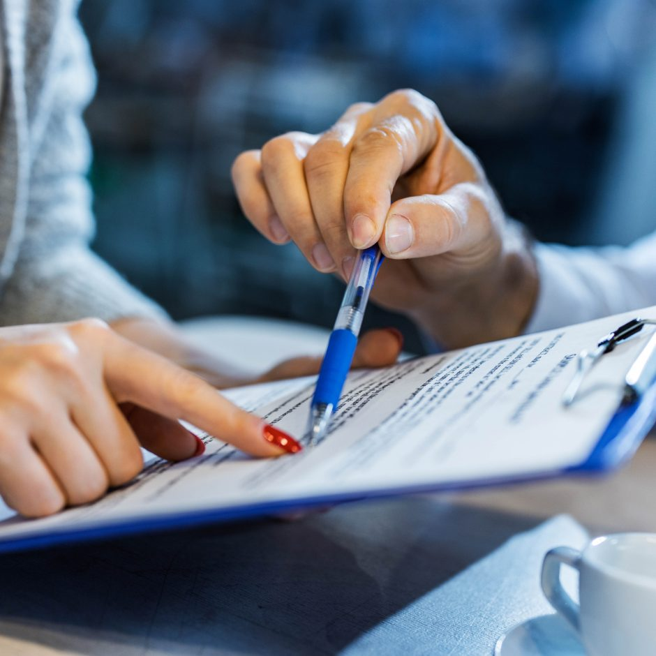 Close up of unrecognizable insurance agent showing his customer where to sign the contract.